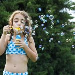 A girl making many small bubbles